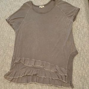 Tunic top with ruffle details and side slit.